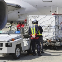 The first batch of Moderna Inc.'s COVID-19 vaccine to arrive in Japan is unloaded at Kansai Airport in Osaka Prefecture on Friday. | KYODO