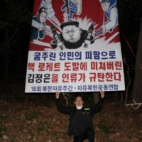 Fighters for a Free North Korea chairman Park Sang-hak releases a banner with a cartoon depicting North Korean leader Kim Jong Un attached to a balloon, at an undisclosed location near the Demilitarized Zone dividing the two Koreas. | FIGHTERS FOR A FREE NORTH KOREA / VIA AFP-JIJI