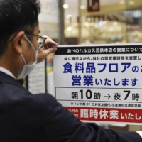 A department store employee puts up a sign on Sunday in the city of Osaka saying that only the food section of the store will be open. | KYODO