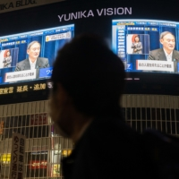 A man walks past TV screens showing Prime Minister Yoshihide Suga speaking during a news conference to announce the extension of a coronavirus state of emergency, in Tokyo on May 7.