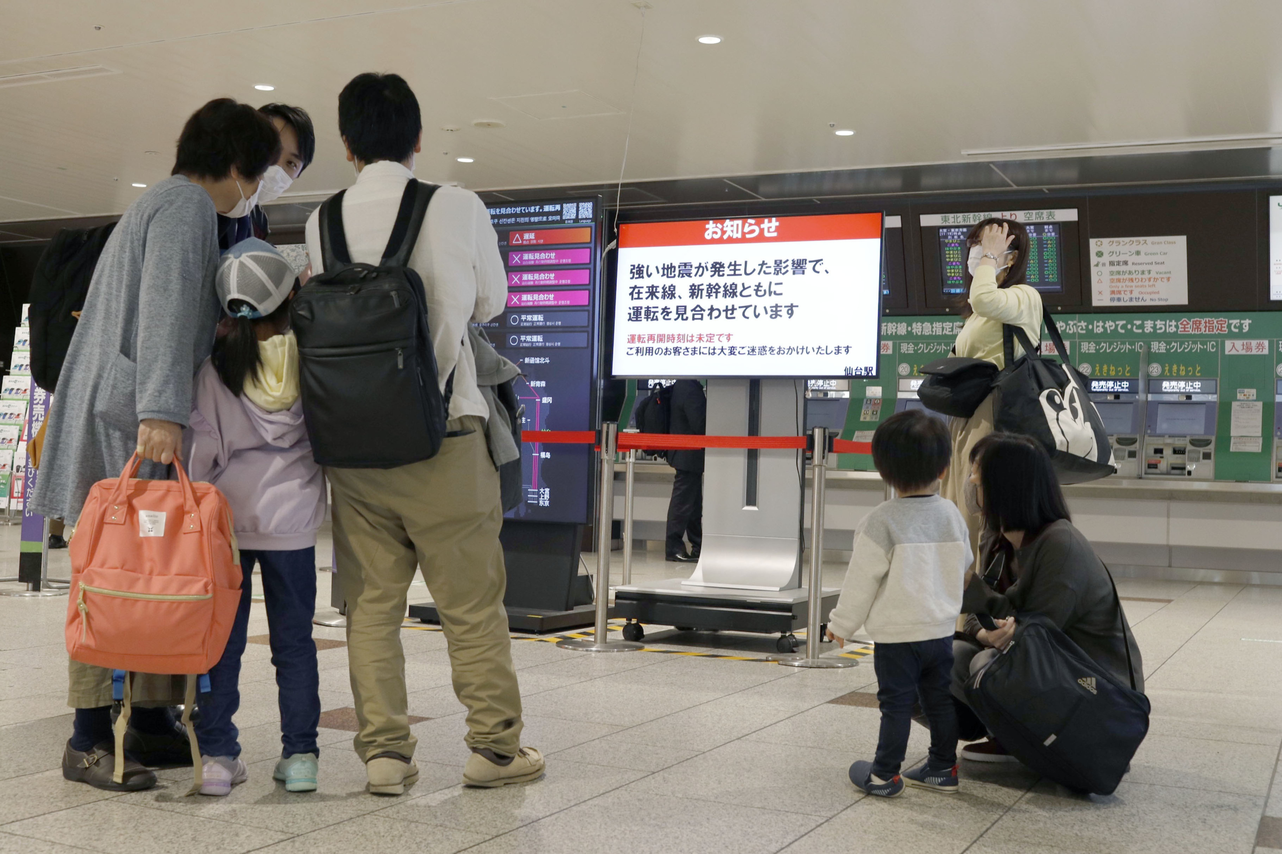 People wait outside the ticket gates of JR Sendai Station after an earthquake shook the area, halting bullet train lines. | KYODO
