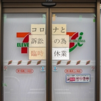 A sign on the entrance of a 7-Eleven store owned by Mitoshi Matsumoto in Osaka says the store is temporarily closed because of the coronavirus and a lawsuit.  | HIROKO MASUIKE / THE NEW YORK TIMES