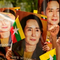 Myanmar migrants in Thailand hold up pictures of detained Myanmar civilian leader Aung San Suu Kyi during a March 7 protest against the military coup in their home country, in front of the United Nations ESCAP building in Bangkok.  | AFP-JIJI