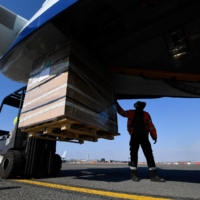 A worker loads medical supplies bound for India at the Oostende-Bruges Airport in Belgium on Friday. | AFP-JIJI