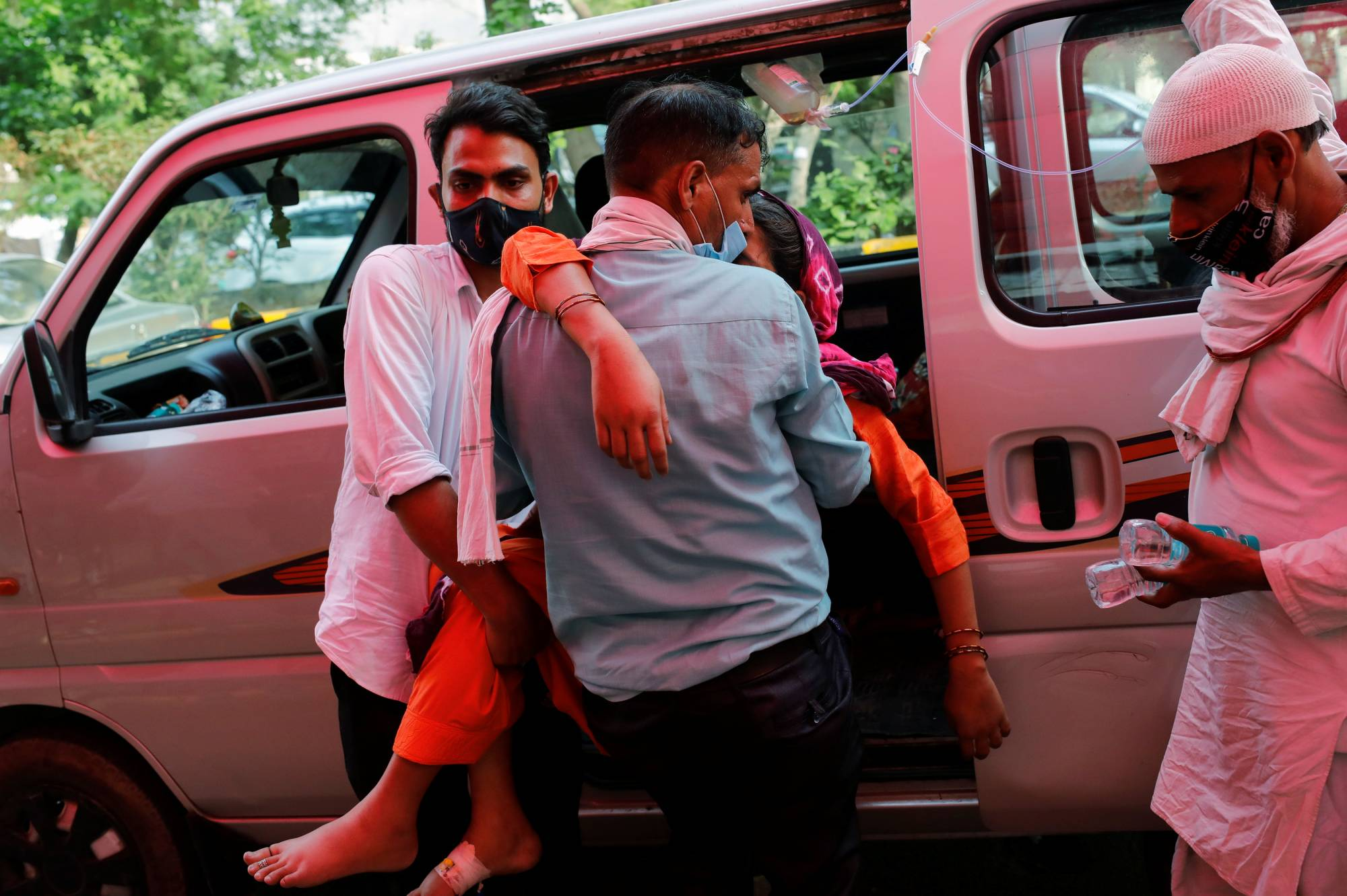A man carries a woman suffering from breathing problems in Ghaziabad, India, on Friday. | REUTERS