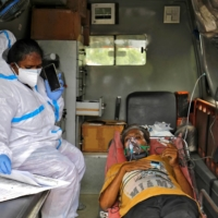 A paramedic checks medical reports of a patient inside an ambulance before heading to a hospital caring for coronavirus patients as COVID-19 spreads in Ahmedabad, India, on Thursday.