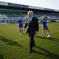 British Prime Minister Boris Johnson speaks with members of the Hartlepool United Ladies Team during a visit in Hartlepool, England, on April 23.  | POOL / VIA REUTERS