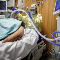 Respiratory Therapist Flor Guevara adjusts a breathing tube for a patient suffering from COVID-19 at Humber River Hospital in Toronto.  | AFP-JIJI