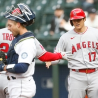Angels designated hitter Shohei Ohtani (right) celebrates with teammate Mike Trout after scoring on Trout's home run against the Mariners on Saturday in Seattle. | USA TODAY / VIA REUTERS