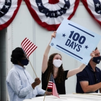 People hold flags and a sign as they attend a Democratic National Committee drive-in rally to celebrate U.S. President Joe Biden's 100th day in office, in Duluth, Georgia, on Thursday. | REUTERS