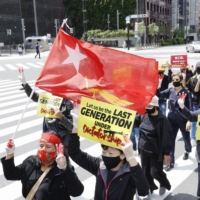 Myanmar residents in Japan march in Tokyo's Ginza district on Sunday to call on the government to recognize Myanmar's National Unity Government. | KYODO