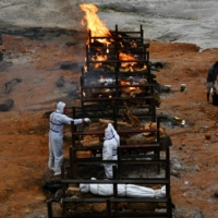 Relatives cremate the body of a person who died due to COVID-19 at a crematorium ground in Giddenahalli village on the outskirts of Bengaluru, India, on Sunday. | REUTERS