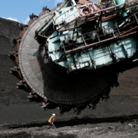 A worker examines a Soviet-made rotary dredge at the Beryozovsky opencast colliery near the Siberian town of Sharypovo, Russia. Elsewhere in Siberia, a vision of Elga as a new coal behemoth epitomizes Moscow's contrarian view of the global energy transition underway.