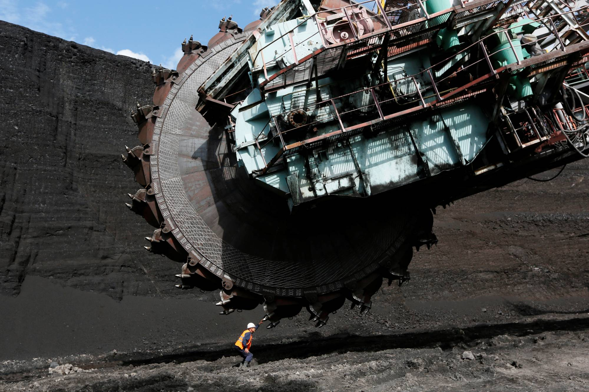 A worker examines a Soviet-made rotary dredge at the Beryozovsky opencast colliery near the Siberian town of Sharypovo, Russia. Elsewhere in Siberia, a vision of Elga as a new coal behemoth epitomizes Moscow's contrarian view of the global energy transition underway.  | REUTERS