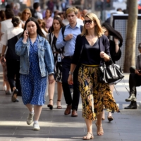 People walk through Melbourne's central business district on April 8. Victoria state has committed to cut greenhouse gas emissions by up to 50% by 2030, based on 2005 levels.  | AFP-JIJI