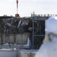 A member of the media, wearing a protective suit and a mask, looks at the No. 3 reactor building at the tsunami-crippled Fukushima No. 1 nuclear power plant in Okuma town, Fukushima prefecture, in February 2016. | REUTERS