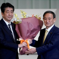 Former Prime Minister Shinzo Abe on Monday expressed support for his successor Yoshihide Suga's re-election as leader of Japan's major ruling party in its leadership race later this year. | POOL / VIA REUTERS