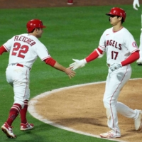 Shohei Ohtani (right) is congratulated by Angels teammate David Fletcher after hitting a two-run home run against the Rays on Monday in Anaheim, California. | USA TODAY / VIA REUTERS