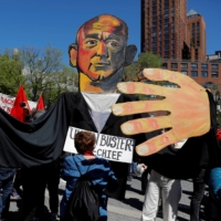 People hold up a large puppet of Amazon CEO Jeff Bezos during a May Day rally on International Workers' Day in New York on Saturday. | REUTERS