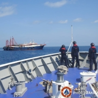 Philippine Coast Guard personnel survey several ships believed to be Chinese militia vessels in the South China Sea on April 27.
