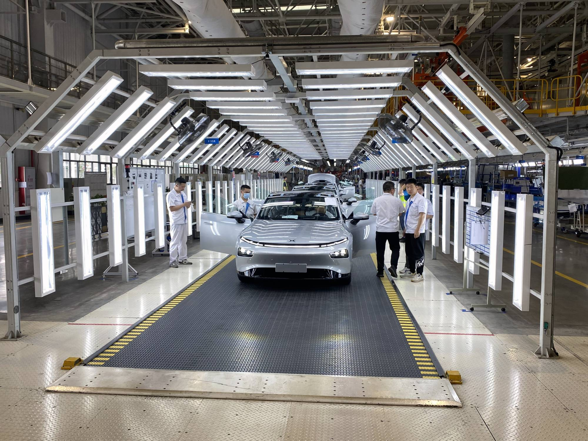 An electric car nears the end of the assembly line at Xpeng's factory in Zhaoqing, China. China will be making over 8 million electric cars a year by 2028, estimates LMC Automotive, a global data firm, compared with 1 million last year. Europe is on track to make 5.7 million fully electric cars by then. | KEITH BRADSHER / THE NEW YORK TIMES