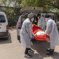 Volunteer health workers from the United Sikh Ambulance Service carry the body of a COVID-19 victim to New Delhi on Tuesday.  |  BLOOMBERG