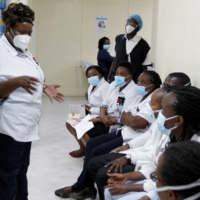 A health worker talks to her colleagues as they prepare to receive the AstraZeneca vaccine under the COVAX program in Nairobi on March 5.  | REUTERS