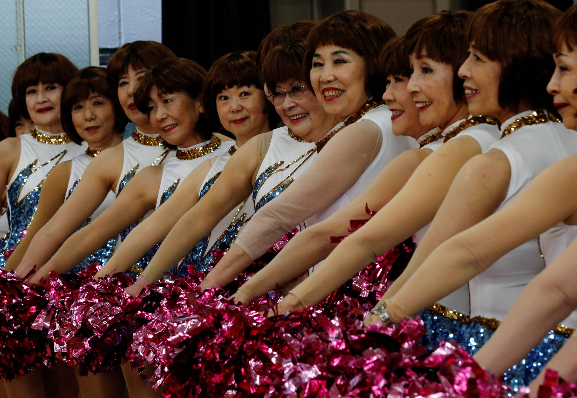 Members of cheer squad Japan Pom Pom post for commemorative photos before filming a dance routine for an online performance in Tokyo, Japan, April 12.   REUTERS