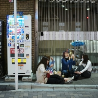 While drinking with friends on the street with booze bought from a convenience store has long been a popular activity in Tokyo's youth culture centers such as Shibuya, the practice has spread in recent weeks as the weather has warmed and restaurants and bars have faced closure requests due to the state of emergency.   RYUSEI TAKAHASHI