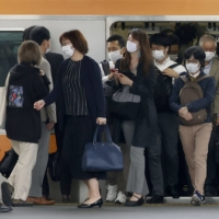 People commute on a crowded train on Thursday in Tokyo.  | KYODO