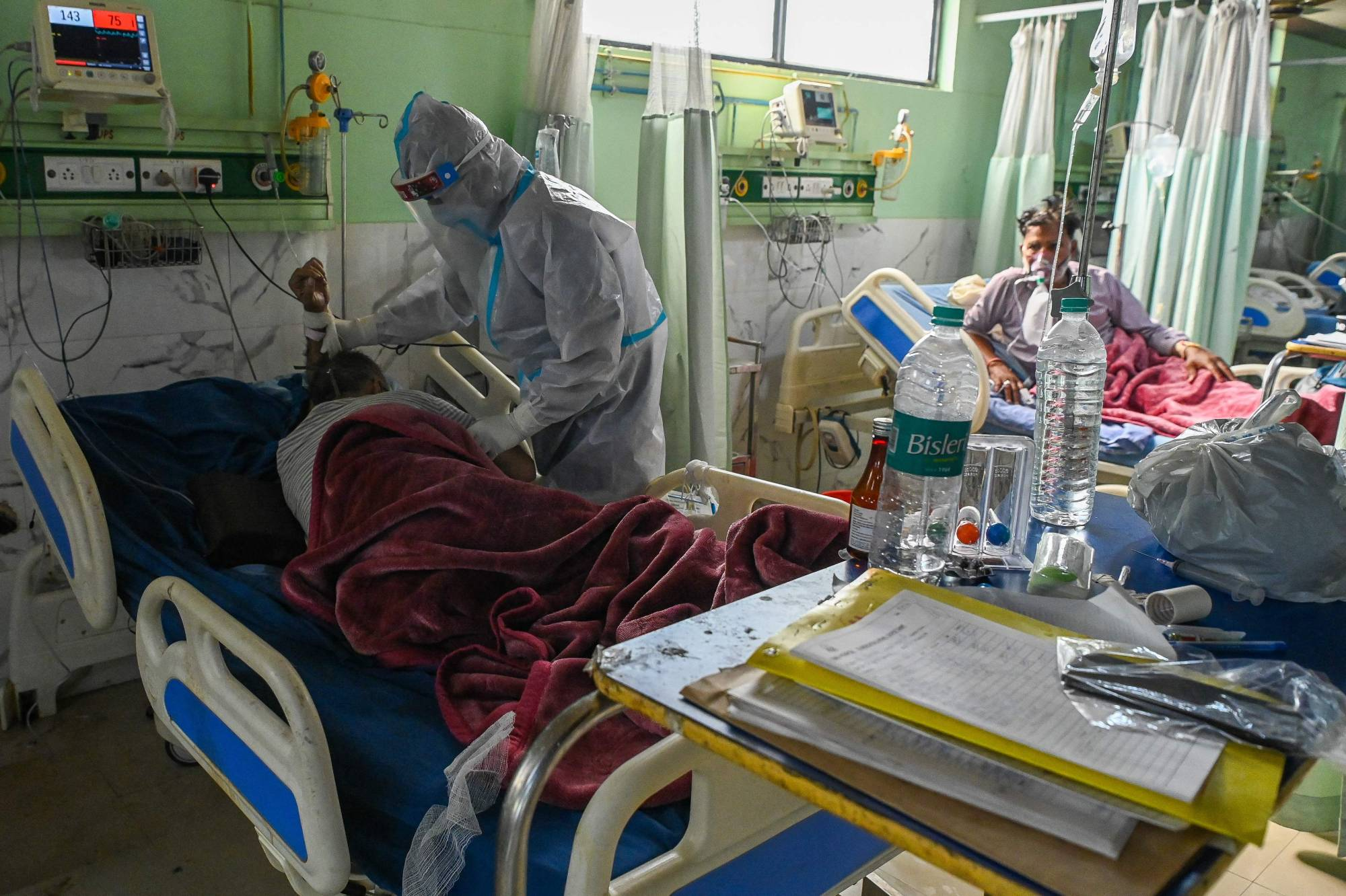 A health worker wearing a personal protective equipment suit tends to a COVID-19 patient inside the Intensive Care Unit of the Teerthanker Mahaveer University hospital in Moradabad, India, on Wednesday.   AFP-JIJI