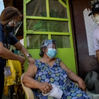 Francia Nolasco, 78, gets a shot of China's Sinovac COVID-19 vaccine in Metro Manila on Wednesday. India's export delays deprived the Philippines of its biggest vaccine order at a time when it is sparring with China over a territorial dispute.   REUTERS