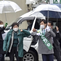 Tokyo Gov. Yuriko Koike (left) touches elbows with an unaffiliated candidate running to represent Tokyo's Chiyoda Ward, supported by Tomin First no Kai, in January. | KYODO
