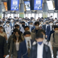 People commute in Tokyo's Shinagawa Station on Friday morning.   KYODO