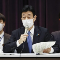 Yasutoshi Nishimura, the minister leading the COVID-19 response, speaks at a meeting of a government advisory panel Friday. | KYODO