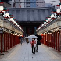 People walk past closed shops in Tokyo's Asakusa district on Friday amid the ongoing coronavirus state of emergency. | REUTERS