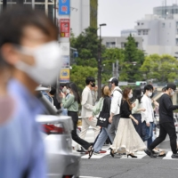 Shoppers crowd a street in Tokyo's Omotesando area on Saturday, a day after the government decided to extend the coronavirus state of emergency in the capital and other prefectures. | KYODO