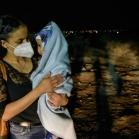 Fatima, 29, sits with her 5-month-old baby, Diego, in the headlights of a U.S. Border Partrol vehicle after arriving in the US illegally across the Rio Grande river in Roma, Texas on March 27. | AFP-JIJI