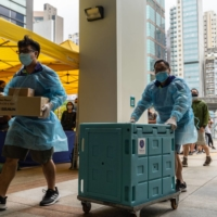 Staff members transport medical materials to a community vaccination center in Hong Kong.   BLOOMBERG
