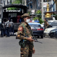 A soldier stands guard as security forces search for protesters in Yangon, Myanmar, on Friday.  | AFP-JIJI