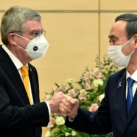 Prime Minister Yoshihide Suga greets International Olympic Committee President Thomas Bach during a meeting in Tokyo last November. | POOL / VIA REUTERS
