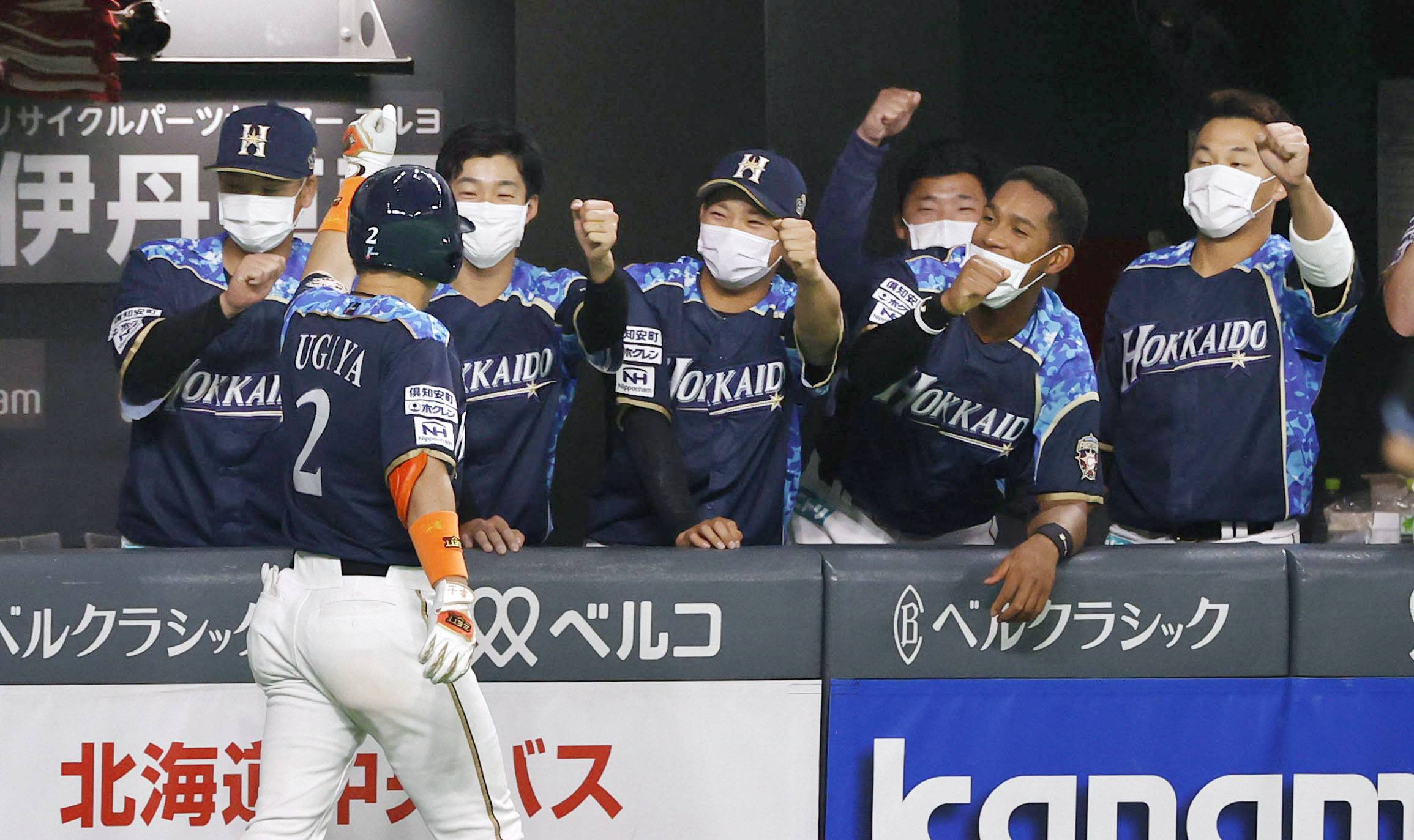 Fighters players congratulate Kenshi Sugiya following his solo home run in the third inning at Sapporo Dome on Friday. | KYODO