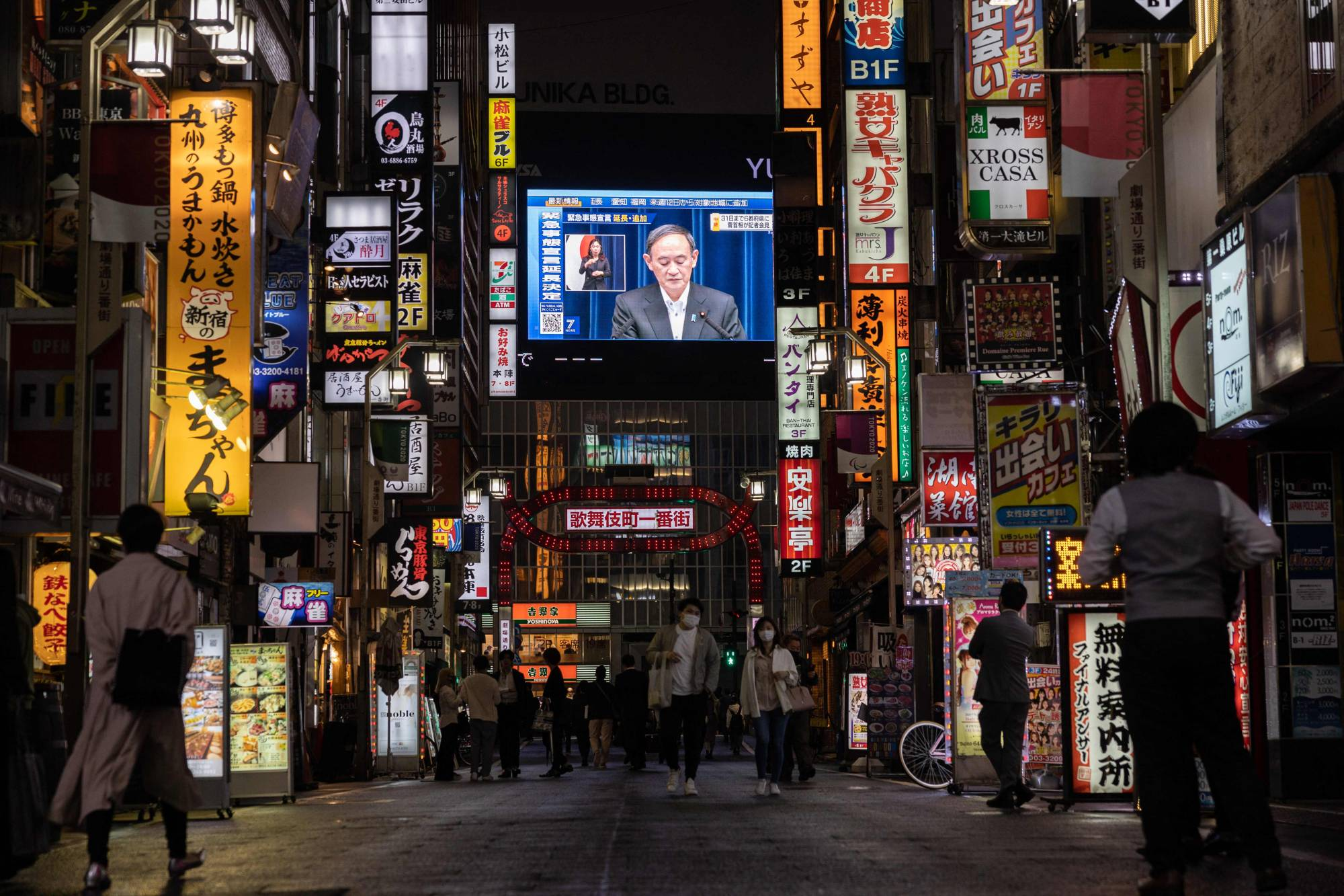 A screen in Tokyo shows Prime Minister Yoshihide Suga speaking during a news conference Friday to announce the extension of a coronavirus state of emergency.   AFP-JIJI