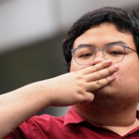 Thai protest leader Parit 'Penguin' Chiwarak flashes a three-finger salute as he arrives at the criminal court in Bangkok in February.  | REUTERS