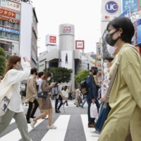 People walk at a scramble crossing near Shibuya Station in Tokyo earlier this month. | KYODO