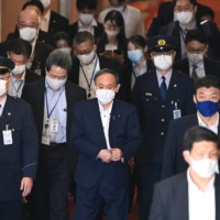 Prime Minister Yoshihide Suga leaves after a parliamentary committee meeting in Tokyo on Monday.