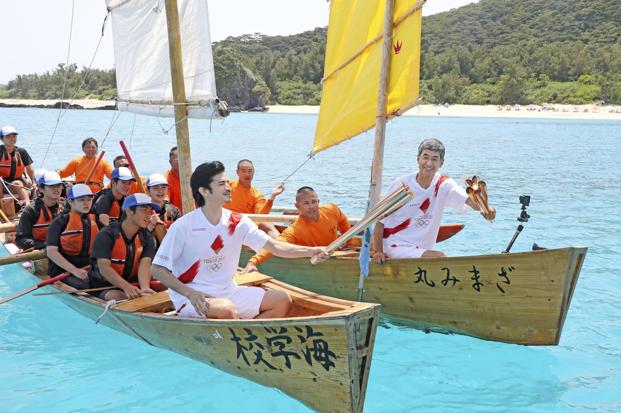 The Olympic flame is passed from torch to torch on traditional rowboats during the Tokyo 2020 Olympics torch relay off Zamami in Okinawa on May 2. | KYODO / VIA REUTERS