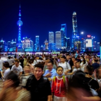 People walk near the Bund, as Shanghai's Lujiazui financial district is seen in the background, on Monday. China on Tuesday announced its slowest population growth since the 1950s, sharply reducing the size of the labor force as the nation ages, and worsening demographic pressures in the economy. | REUTERS