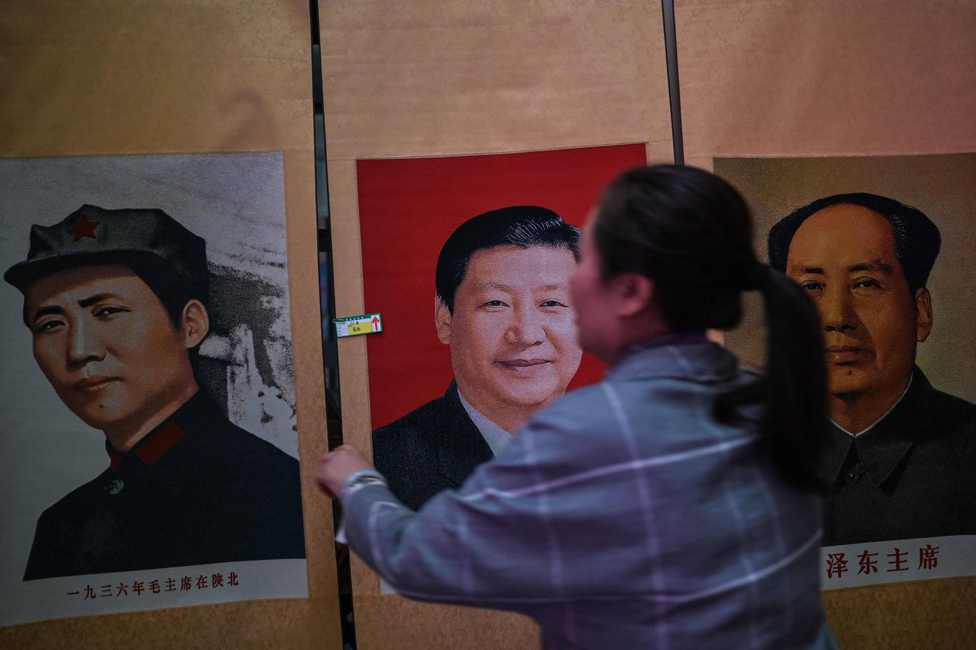 A woman adjusts a portrait of Chinese President Xi Jinping between two pictures of former leader Mao Zedong at the Dongfanghong Theater in Yan'an, China, on Saturday, ahead of the 100th anniversary of the Chinese Communist Party's founding in July.  | AFP-JIJI