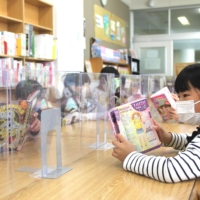 Students read books in a school library in Sendai. | KAHOKU SHIMPO